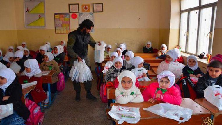 Op deze in 2016 gepubliceerde foto van een militante website, is volgens persbureau AP een klaslokaal in de door IS gecontroleerde Iraakse stad Mosul te zien. Een IS-lid deelt onderwijsbenodigdheden uit. Beeld ap