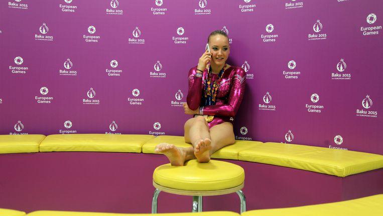 Lieke Wevers, gouden medaille om haar nek, doet zaterdag per telefoon opgetogen haar verhaal. Beeld   Ad Nuis