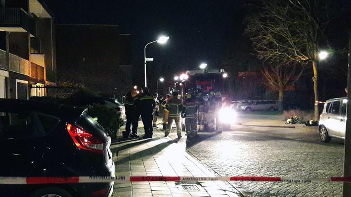 Brandweer en politiemensen staan voor de woning op straat.