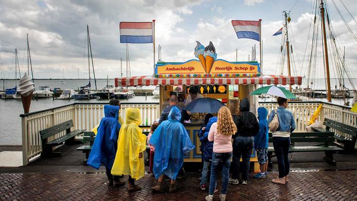 Toeristen met paraplu's trotseren de regen in de oude haven van Volendam.