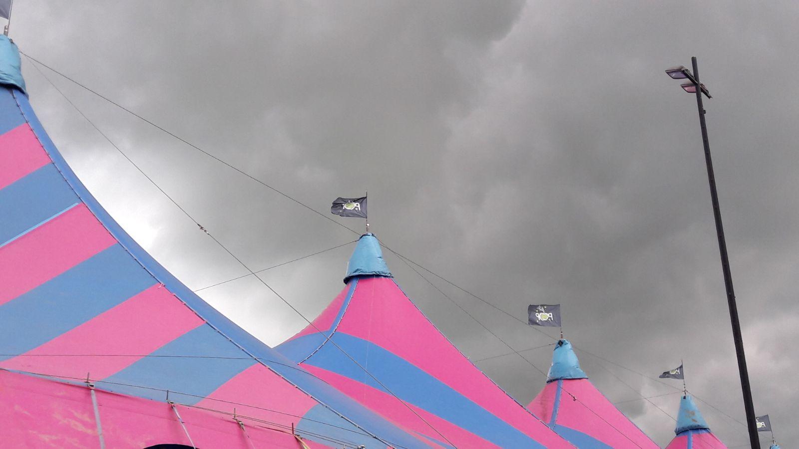 Donkere wolken boven de megatent.