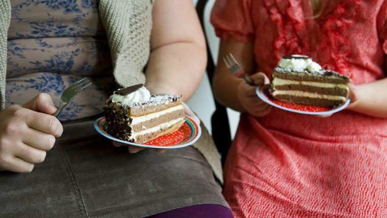Een vrouw en een meisje eten samen gebak. Beeld anp