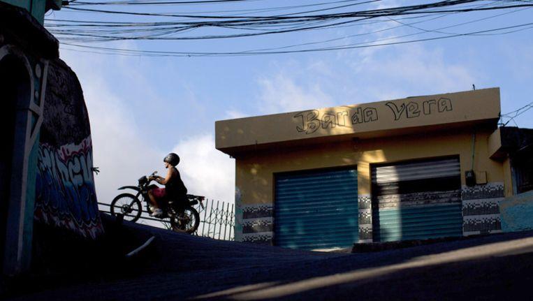 Een man rijdt op zijn motor in de sloppenwijk Rocinha in Rio de Janeiro Beeld ap