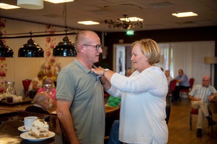 Gerrit Jannink krijgt de vrijwilligersspeld van de gemeente Wierden opgespeld door zijn vrouw.