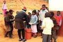 Schoolkinderen staan in de rij voor een bordje eten. AFP PHOTO