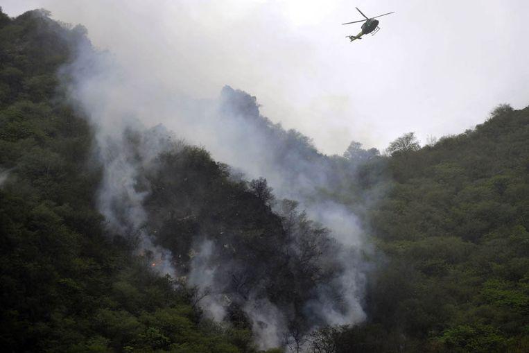 Een helikopter cirkelt rondom de rampplek in de heuvels rondom Islamabad (AFP) Beeld AFP