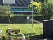 Er wordt volop gesproeid in de tuin van de Nicolaaskerk in Denekamp, maar wel met grondwater