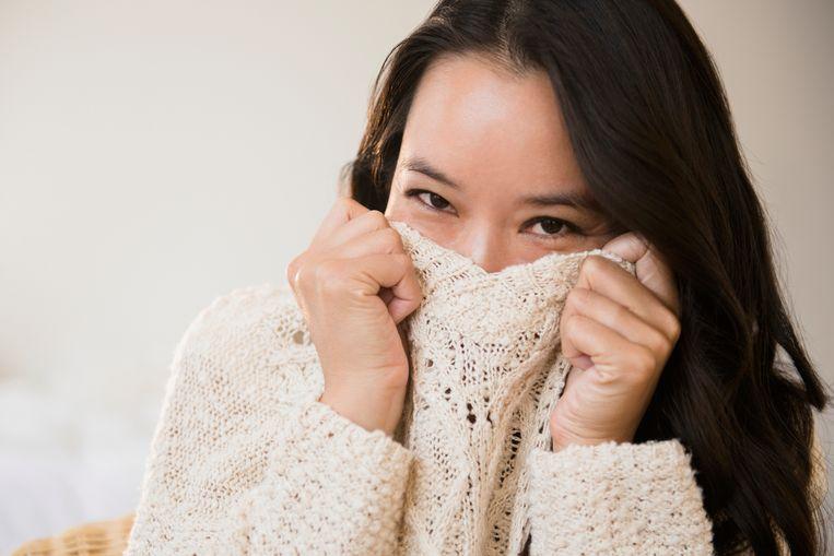 Chinese woman peeking over collar of sweater