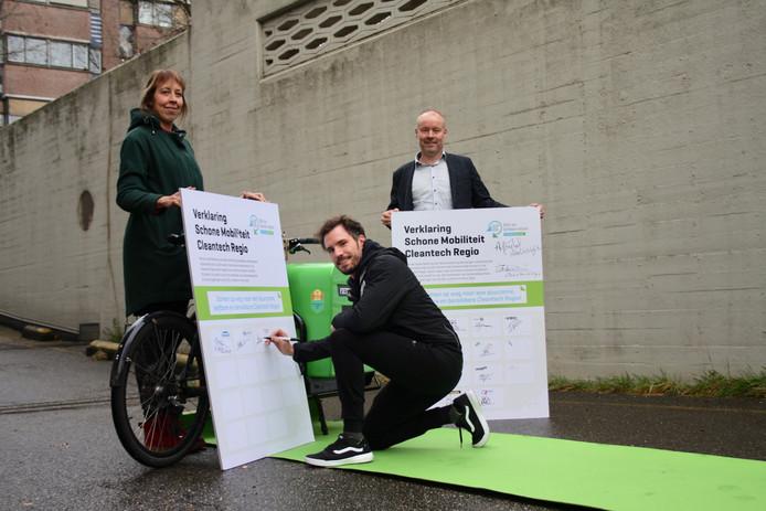 Peter Dorenbos (midden) van Fietskoeriers Apeldoorn ondertekent de Verklaring Schone Mobiliteit.
