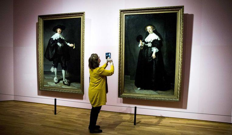 Een bewonderaar staat voor 'Portret van Marten Soolmans' (links) en 'Portret van Oopjen Coppit' (rechts) van Rembrandt, bij een eerdere expositie in het Rijksmuseum.  Beeld null