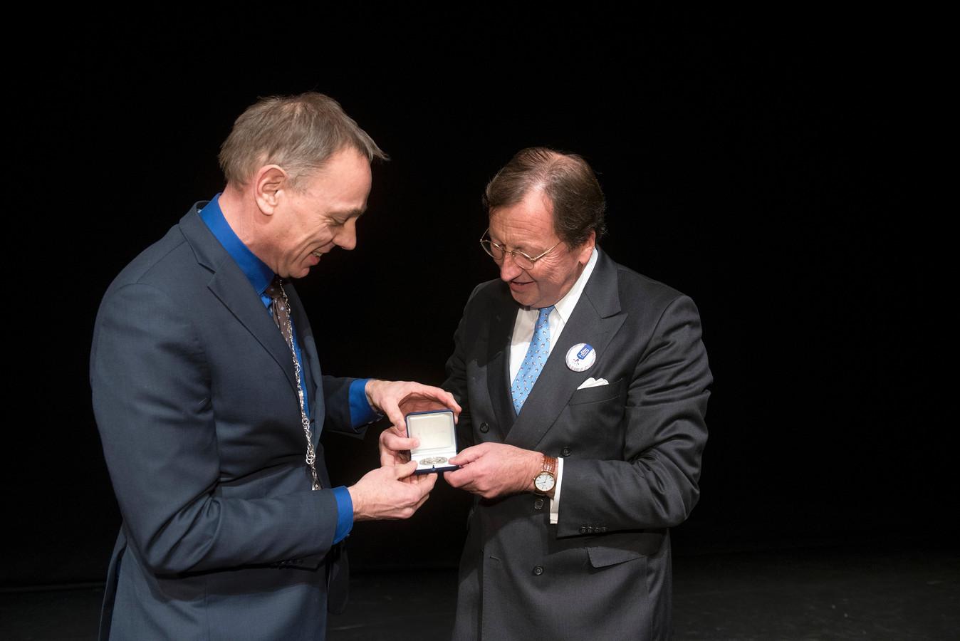 Bart van Meer krijgt de stadspenning uit handen van wethouder König.