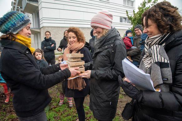 Ann Sels overhandigde 535 handtekeningen en een houten cadeautje aan schepenen Storms, Decruynaere en De Bruycker.