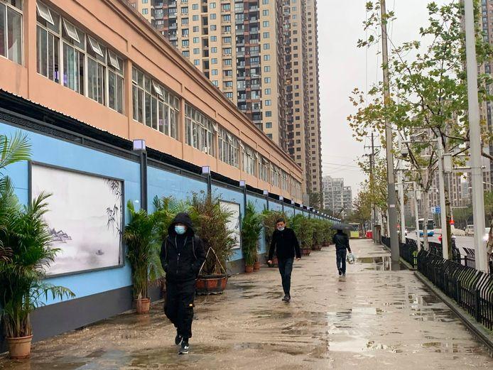 Bewoners van Wuhan lopen langs de gesloten voedselmarkt van Wuhan, de Huanan Seafood Wholesale Market, een van de plekken waar het coronavirus kan zijn ontstaan.