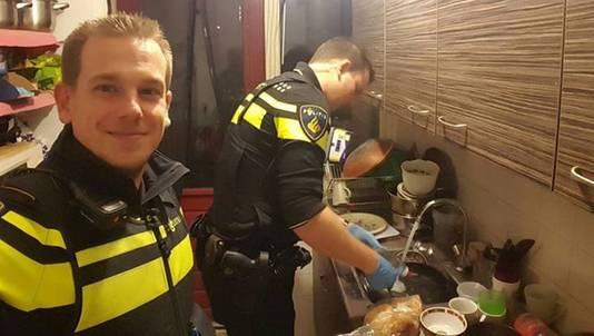 De agenten doen de afwas nadat de moeder van het gezin met spoed naar het ziekenhuis moest.