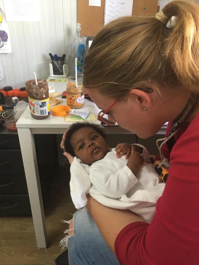 Debora Molenaar uit Bruinisse ontfermt zich in het Griekse kamp Moria over één van de jongste vluchtelingen, die afgelopen zomer in het kamp, buiten op het grind, werd geboren.