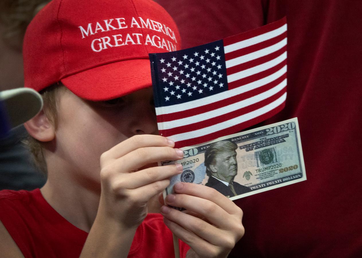 Een jeugdige Trump-aanhanger houdt een Amerikaanse vlag en een dollarbiljet met het portret van de president omhoog.