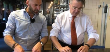 Commissaris van de Koning Wim van der Donk maakt worstenbroodje bij Houben in Eindhoven