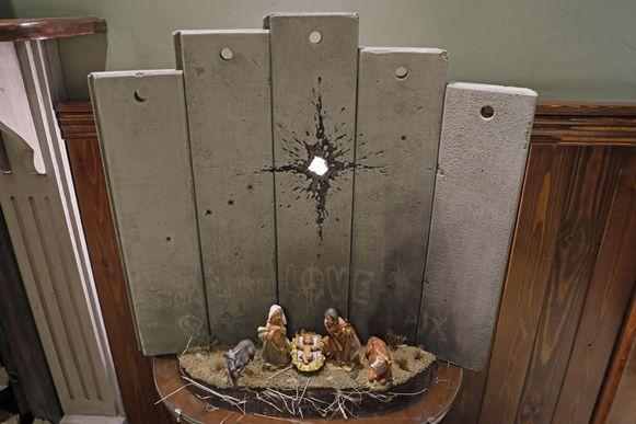 Het kunstwerk genaamd het 'Litteken van Bethlehem' van de straatkunstenaar Banksy in het Walled-Off Hotel in Bethlehem op de Westelijke Jordaanoever.