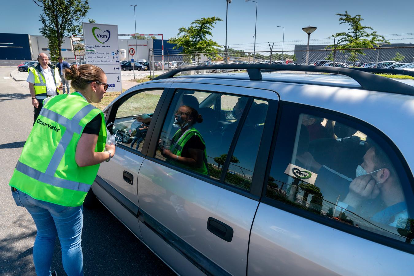 Bij de ingang van Vion in Boxtel wordt het vervoer van personeel gecontroleerd. Medewerkers kunnen er bovendien extra mondkapjes krijgen.