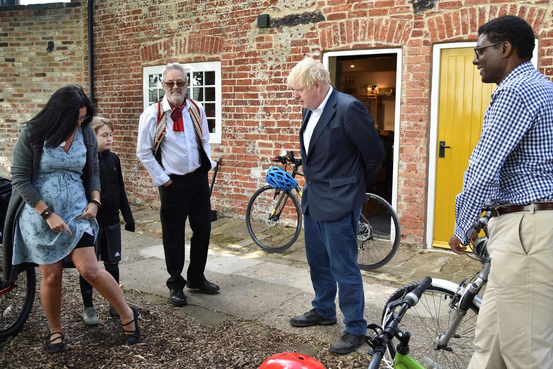 Boris Johnson (tweede van rechts) en partijgenoot Darren Henry (rechts) proberen mensen in Beeston dinsdag aan het fietsen te krijgen. Beeld Rui Vieira / AFP