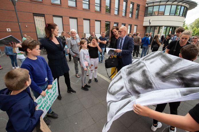Raadsleden, zoals Beent Keulen (VVD, met stropdas) worden bij aankomst aangeklampt door demonstrerende woonwagenbewoners.