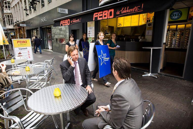 Barry Madlener, PVV-lijsttrekker voor de Europese Verkiezingen, belt op het terras van de snackbar van Febo, recht tegenover de ingang van de Tweede Kamer. (Martijn Beekman / de Volkskrant) Beeld Martijn Beekman