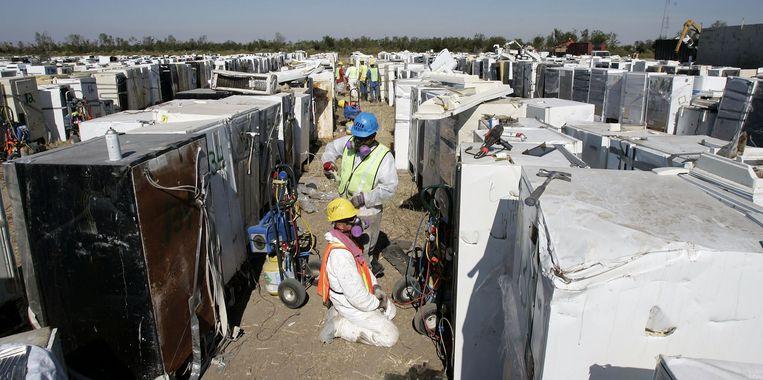 Werkers bereiden zich voor om cfk's van koelkasten en ander witgoed te verwijderen.  Beeld Getty Images