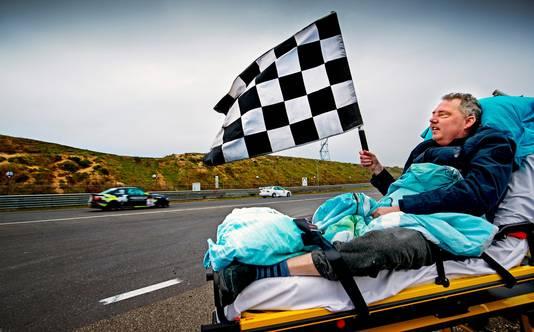 Met een finishvlag zwaait Marco Scheffers langs de kant naar de voorbij razende raceauto's.
