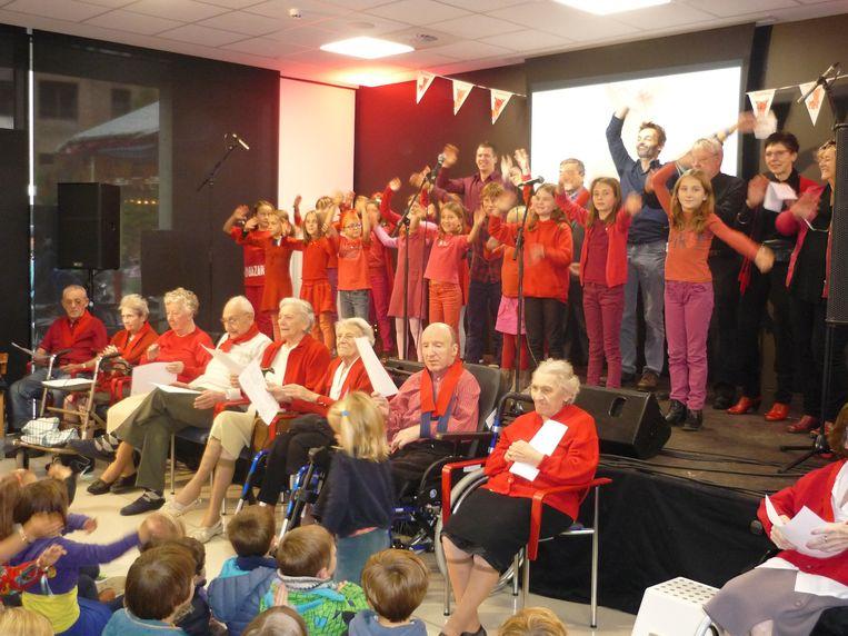 Zowel de bewoners van woonzorgcentrum Remy als de kinderen van de Abdijschool in Vlierbeek zingen het gloednieuwe Rode Hond-lied uit volle borst mee.