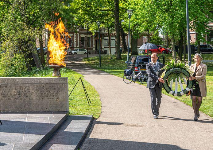 Burgemeester Peter Snijders en zijn vrouw Geeke leggen een krans tijdens de stille dodenherdenking in het Ter Pelkwijkpark in Zwolle.