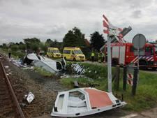 Bestelbusje op kant in de sloot na botsing met trein in Opheusden
