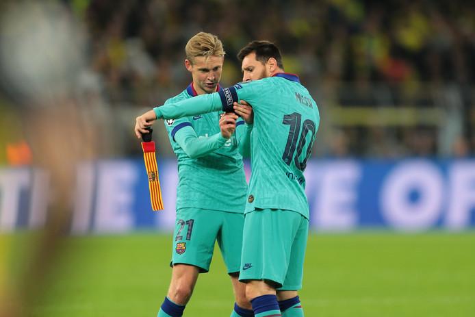 Frenkie de Jong doet de aanvoerdersband om de arm van Lionel Messi.