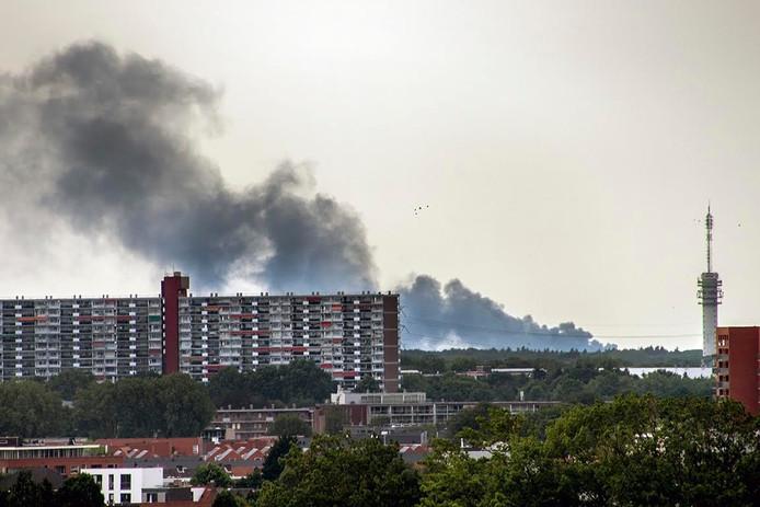 Op dik 20 kilometer afstand in het centrum van Tilburg zijn grote zwarte rookwolken van de brand in Waalwijk te zien.