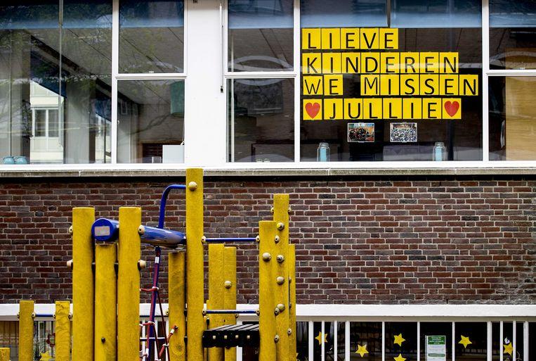 De tekst 'Lieve kinderen we missen jullie' hangt voor een raam bij een school in Rotterdam. Beeld ANP