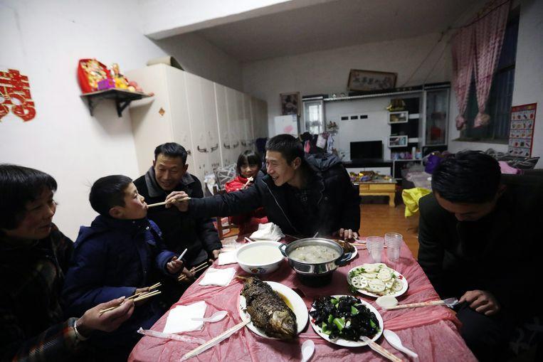 Wang Pengfei geeft zijn zoon te eten. Hij is maar één keer per jaar thuis. Beeld EPA