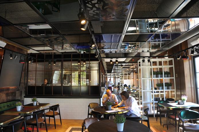 Twee heren van de keukenbrigade nemen de inventarislijsten en menukaarten door in het restaurant van Blur. Door de glazen ruitjes zijn de activiteiten van de koks te volgen. Achter de keuken zijn het broodjesafhaalpunt, de bar en het loungecafé te vinden.