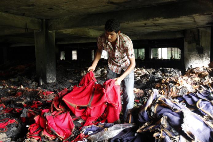 Een werknemer kijkt naar verbrande kledingstukken in een kledingfabriek in Dhaka, Bangladesh. Zeker 100 mensen kwamen er eind 2012 om het leven bij de brand.