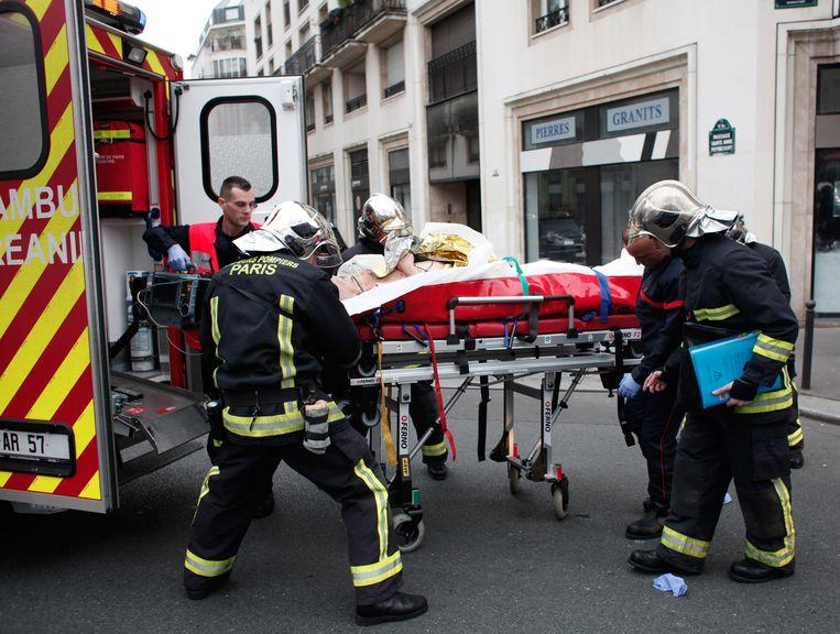 Een gewonde van de aanslag wordt op een brancard een ambulance ingereden. Beeld ap