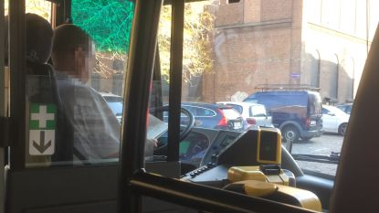 Chauffeur De Lijn leest boekje achter stuur