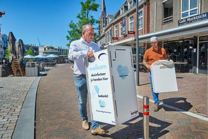 Dirk Lammers (links) en Jeroen van den Nieuwehuizen plaatsen voorzieningen voor het desinfecteren van de handen. Dit is een van de maatregelen tegen corona bij de terrassen op de Markt in Veghel. Archiefbeeld: Van Assendelft/Jeroen Appels