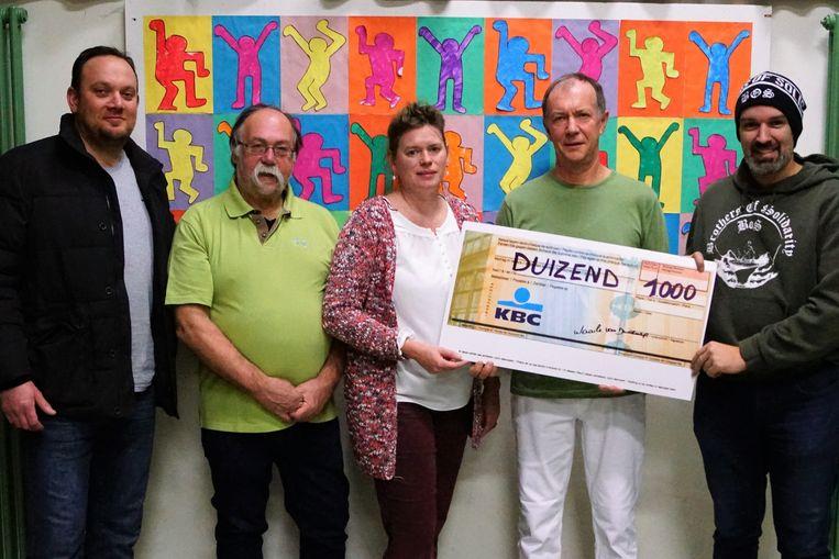 Marc Slootmans, Edgard Deloor en Ingrid Praet van de toneelkring Waaile van Dwoeurp overhandigen de cheque aan David Goubert en Thomas Degrève van Brothers of Solidarity.