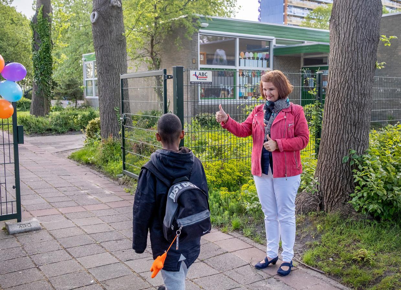Directrice Bernadette von den Benken verwelkomt de kinderen bij het hek.