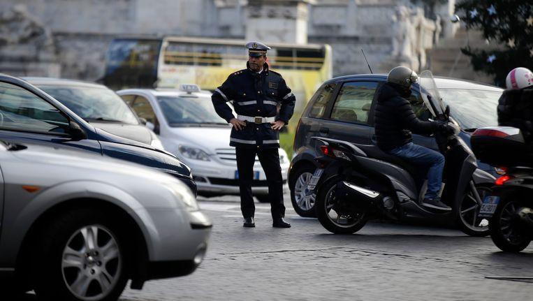 Een politie agent regelt het verkeer in Rome. Rome en Milaan hebben besloten dat mensen voor een aantal dagen hun auto moeten laten staan om de vervuiling in de steden tegen te gaan. Beeld ap