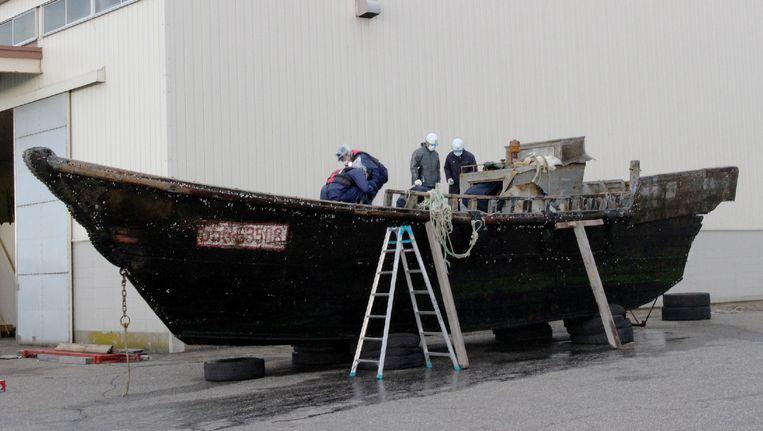 De Japanse kustwacht onderzoekt één van de boten, die werd aangetroffen voor de kust van havenstad Fukui. Beeld AFP