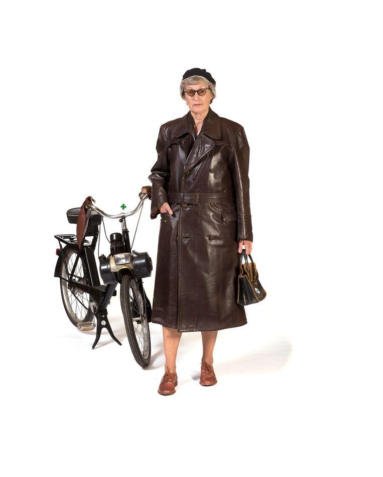1960 Uniform van wijkverpleegster: zwarte leren jas, zwarte muts met witte rand en solex met leren handkappen. Beeld Inge Hondebrink