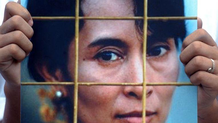 Een activist houdt een portret van Aung San Suu Kyi omhoog. Beeld null