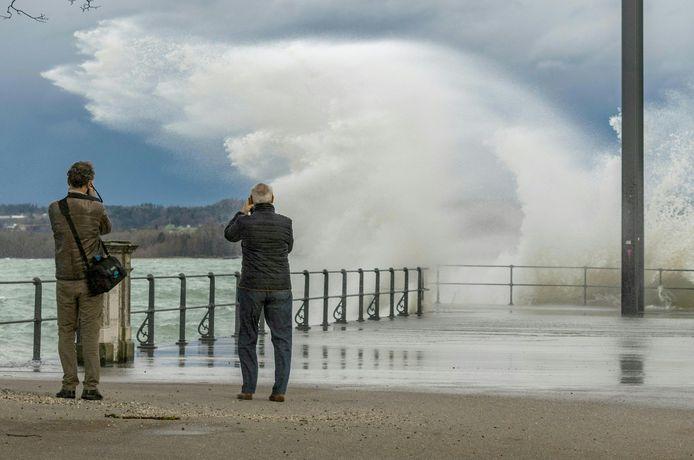 Twee ramptoeristen tijdens het fotograferen van de effecten van storm Ciara, gisteren bij de Bodensee in het Oostenrijkse Bregenz.