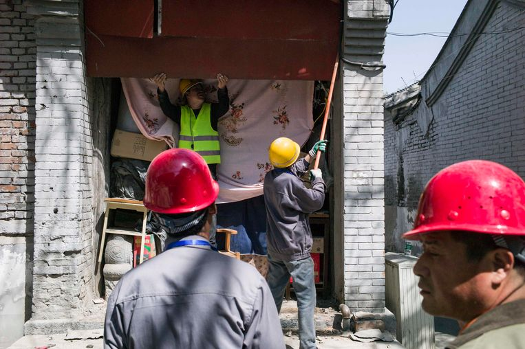 Bouwvakkers blokkeren de ingang van een winkel in Peking. Het is een veelgebruikte methode van het stadsbestuur om makkelijk van winkeliers in woonwijken af te komen. Beeld AFP