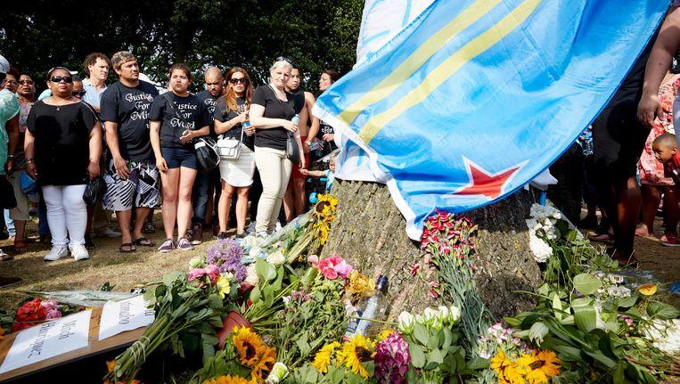 Deelnemers aan de stille tocht voor Mitch Henriquez leggen bloemen en spandoeken neer in het Zuiderpark. Beeld anp