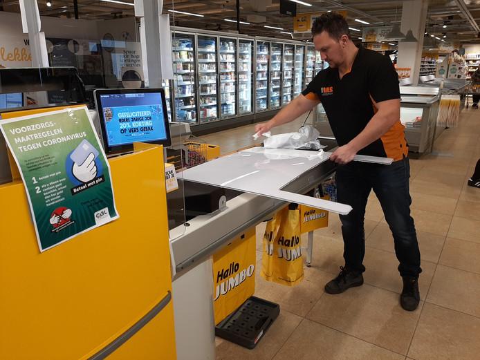 Arnaud Vos verwijdert de beschermingsfolie van een kunststof plaat, die besmetting met corona moet voorkomen.